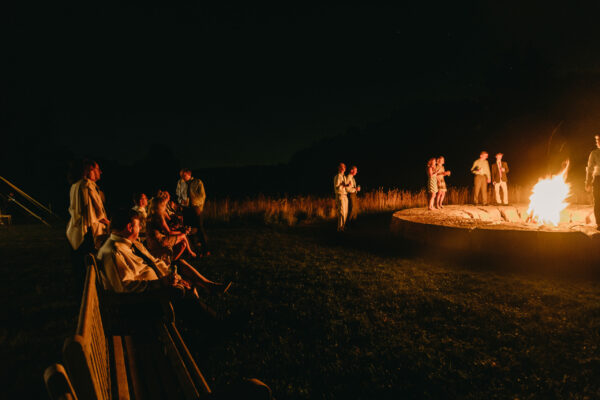 Wedding guests at evening bonfire