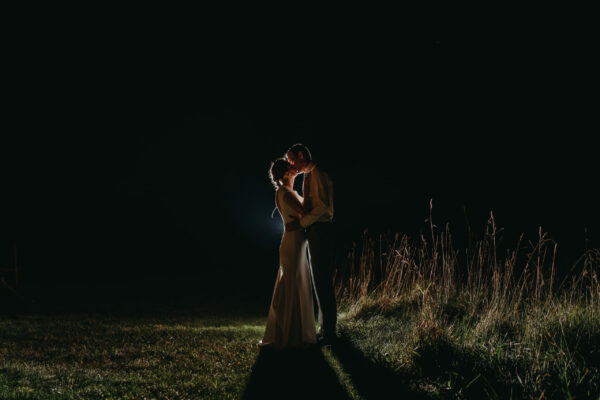 Bride and groom kissing at night backlit